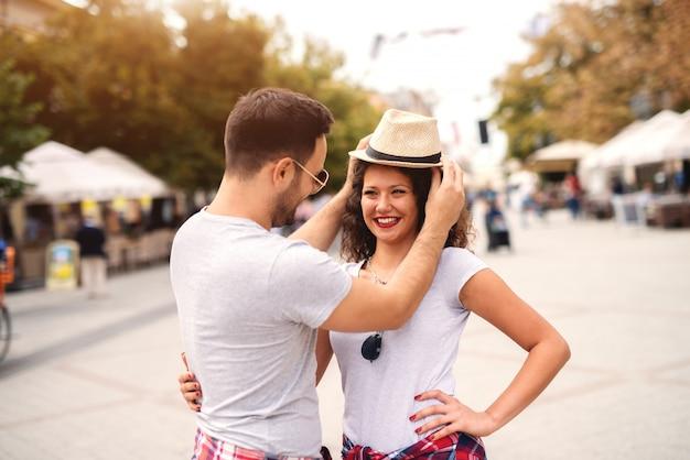 通りに立っているガールフレンドの頭に帽子をかぶる男。夏の旅行のコンセプトです。