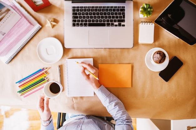 オフィスデスクでコーヒーブレークを持っている間ノートで組織計画を書く女性デザイナーの平面図。