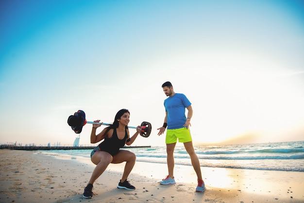 素晴らしい日の出でバーベルとしゃがむやる気のある筋肉の強い女性