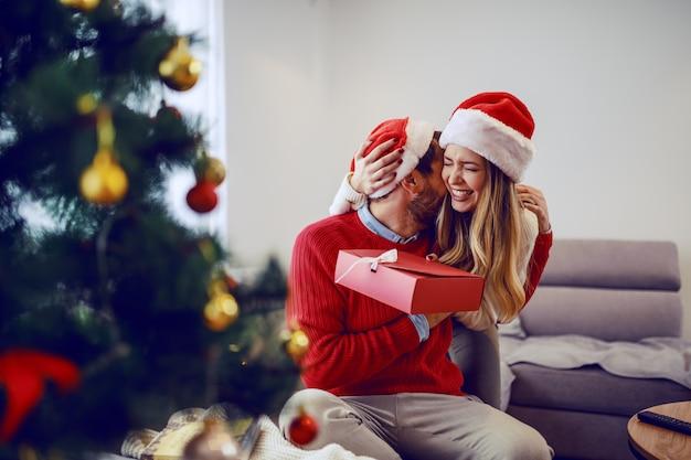 リビングルームのソファーに座って、贈り物を保持し、彼のガールフレンドと抱き締めて大喜びのハンサムなひげを生やした男。どちらも頭にサンタ帽子をかぶっています。手前にはクリスマスツリーがあります。リビングルームのインテリア。