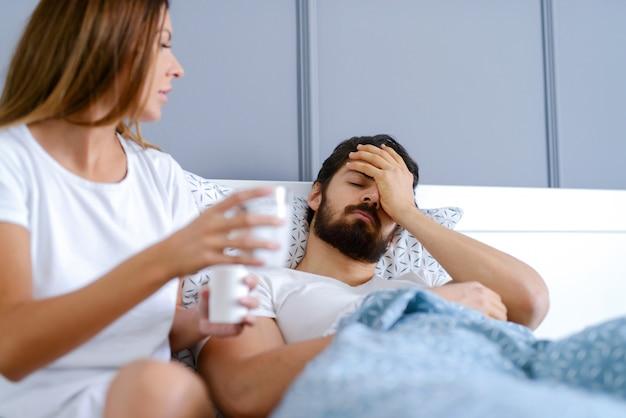 Женщина приносит своему парню лекарства в постели.