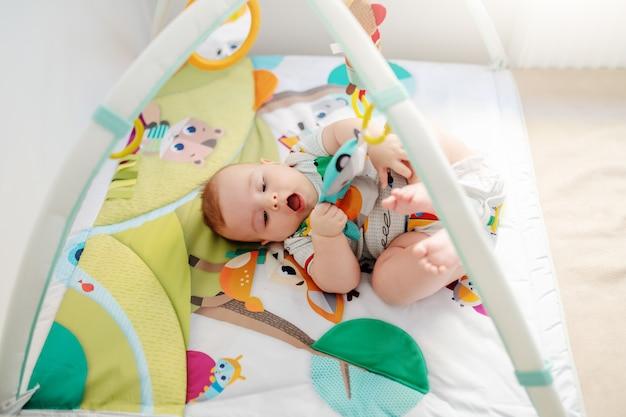 ベビーベッドで遊ぶ赤ちゃん。