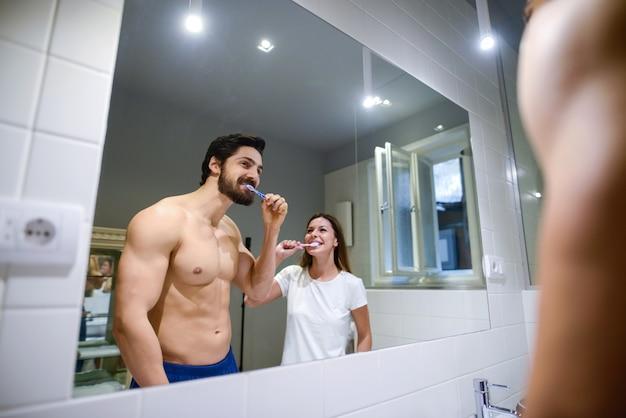 Пара мытья зубов в ванной комнате.