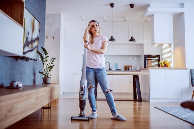 彼女の家の掃除フォームを休んで疲れた主婦。