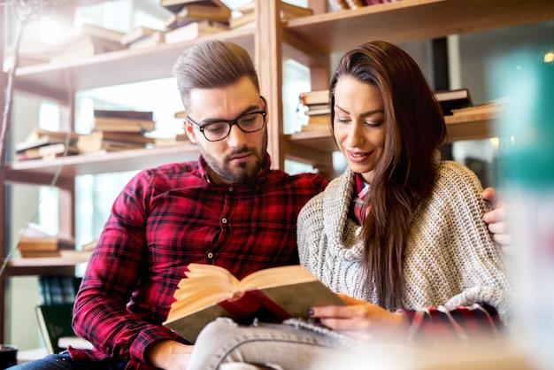 図書館で本を読んでいるカップル。