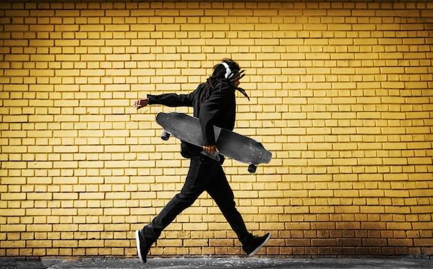 Красивый молодой конькобежец дреды с наушниками, работает в костюме возле желтой стены на улице.