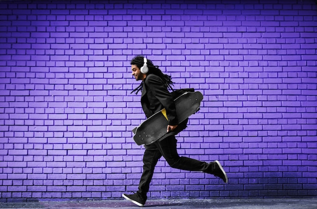 Красивый молодой дреды фигурист с наушниками работает в костюме возле фиолетовой стены на улице.
