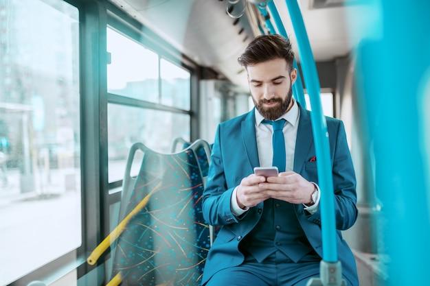 公共バスに座っているとスマートフォンを使用して青いスーツの魅力的な深刻な白人ひげを生やした青年実業家。