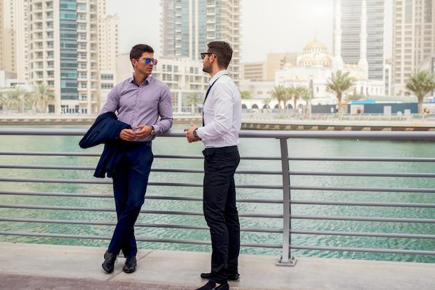 Два молодых бизнесмена в полном костюме обсуждают планы. концепция работы