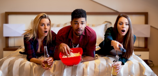 ベッドに横になっている友人、ホラー映画を見て軽食や飲み物を持っている