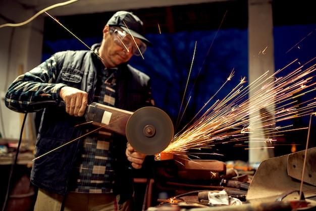 Мастер пилят металл с точильщиком на мастерской.