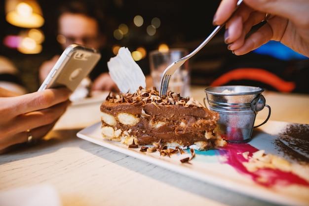 Закройте вверх по взгляду фокуса шоколадного торта пустыни с милой малой чонсервной банкой молока на плите в ресторане.