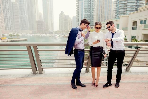 外で話しているビジネス人々のグループ。携帯電話を見てください。