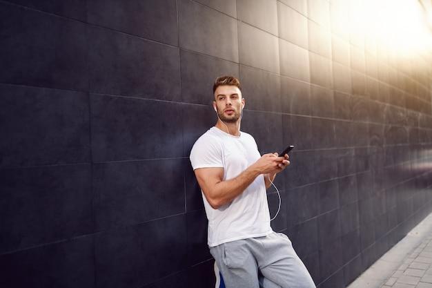 Красивый кавказский бородатый белокурый мышечный человек в футболке держа умный телефон пока полагающся на стене и смотрящ прочь. в ушах наушники.