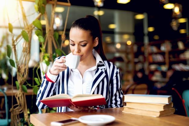 Привлекательная молодая женщина в элегантной одежде, пить кофе во время чтения