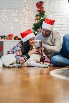 自宅でクリスマス休暇のための愛らしい白い犬を抱きしめる若いかわいい笑顔のカップル。