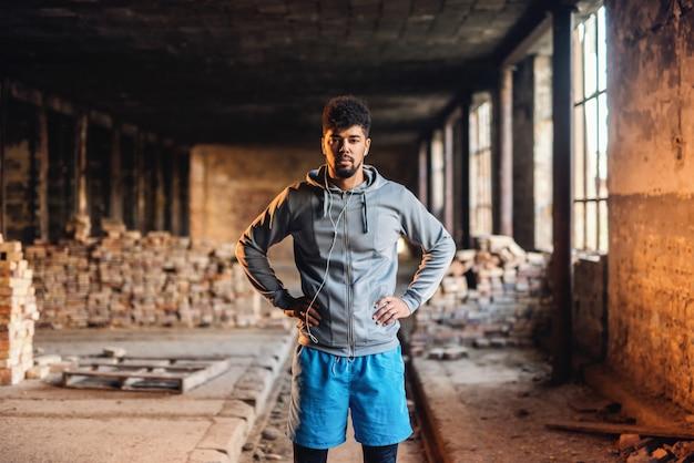 Портрет афроамериканца спортивный человек с серьезным лицом, держась за руки на бедрах и стоя в старой кирпичной фабрике.
