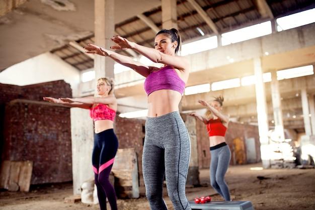 古い放棄された格納庫での演習を行う魅力的な若いフィットネス女性。