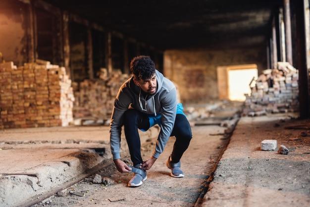 Портрет афро-американского парня кладя на тапку пока заискивающ в старой фабрике кирпича. наушники включены.