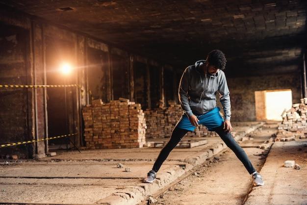 Афро-американский спортивный человек в спортивной одежде, протягивая ноги в старой кирпичной фабрике. концепция здорового образа жизни.