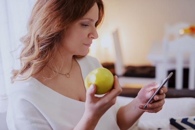 Профиль красивой кавказской беременной женщины сидя в гостиной, используя умный телефон и есть яблоко.