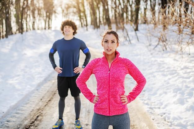スポーツウェアの美しい白人のスポーティなブルネットを腰に手で道の上に立って、実行後に休んでフィットします。背景には彼女の男性の友人も休んでいます。冬。屋外フィットネス。