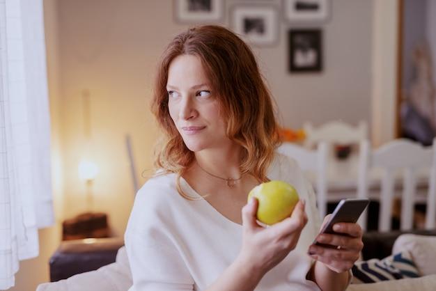 Красивая кавказская беременная женщина сидя в живущей комнате, используя умный телефон и есть яблоко.