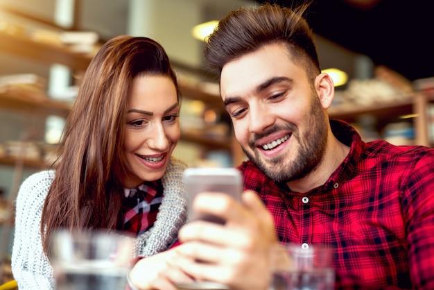 Молодые люди в клетчатых рубашках развлекаются в кафе