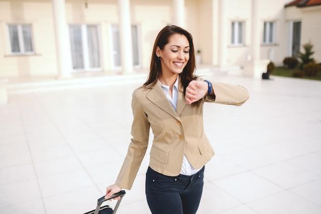 Красивая усмехаясь кавказская коммерсантка одела умное вскользь смотря наручные часы и вытягивая багаж пока идущ снаружи. концепция деловой поездки.