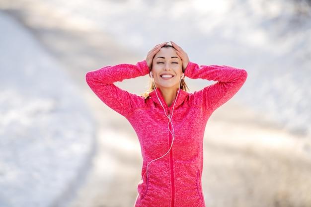 Брюнетка шикарной привлекательной пригонки кавказская стоя в спортивной одежде и с хвостиком наслаждаясь музыкой пока отдыхающ после бежать. зимний. концепция открытый фитнес.