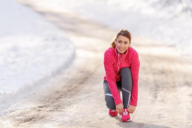 Женщина связывая шнурок пока заискивающ на следе на зиме. концепция открытый фитнес.