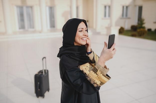彼女の家の前に立っている間タクシーを呼び出すためにスマートフォンを使用して伝統的な摩耗でゴージャスなイスラム教徒の女性の肖像画。バックグラウンドで荷物。