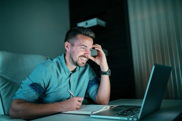 ノートパソコンで見ていると夜遅くオフィスに座っている間ノートを書いている従業員の笑顔。