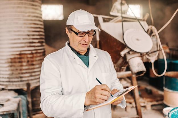 帽子をかぶった獣医、白い制服、眼鏡が納屋に立ったまま動物検査の結果を書きます。