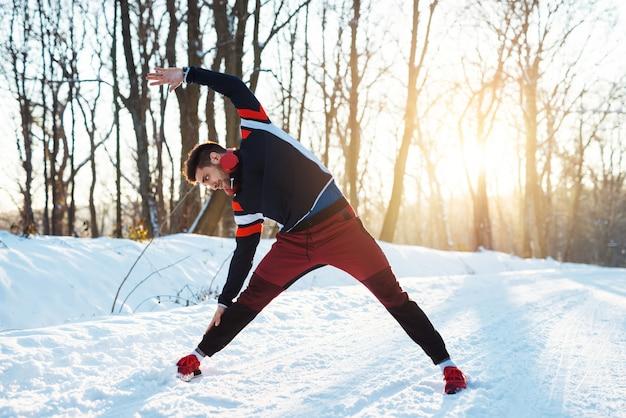 Гибкий молодой бегун в спортивной одежде с наушниками, растяжения с поднятой рукой на заснеженной зимней дороге в первой половине дня.