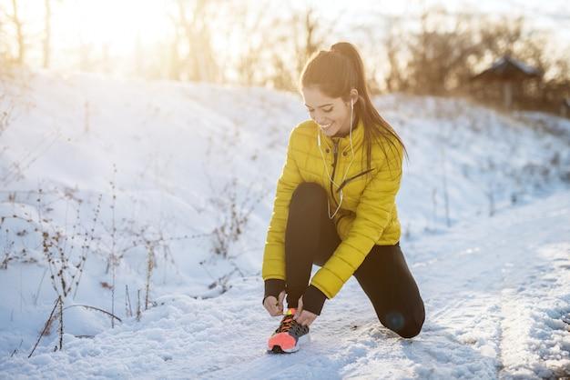 Молодая и сосредоточенная спортивная активная девушка с хвостиком, присевшим в зимней спортивной одежде снежной натуры на дороге и завязывающим шнурки на кроссовках.