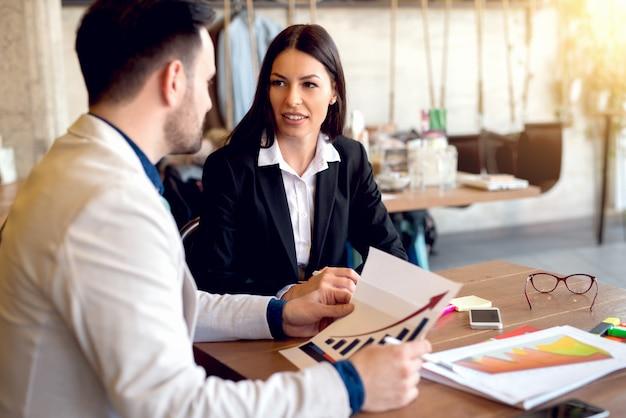 Боковой снимок мужчины и женщины в костюмах обсуждают работу