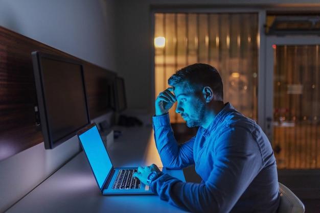 Серьезный кавказский трудолюбивый работник сидит в офисе поздно вечером и заканчивая проект на ноутбуке.