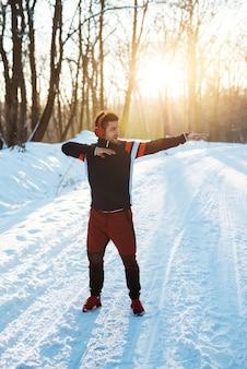 Спортивный человек, протягивающий руки перед утренней тренировкой на красивом восходе солнца