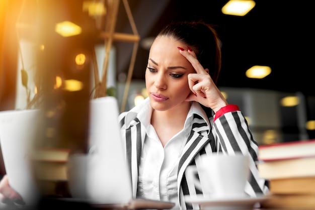 電話を待っているラップトップを見て不幸な女性。レストランのコーヒーはオフィスの外で遅くまで働いています。