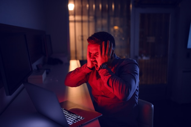 Человек смотрит на ноутбук и сидит в офисе поздно ночью.
