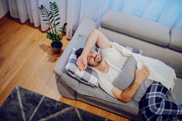 Взгляд сверху очень больного кавказского человека в пижамах и покрытого с одеялом лежа на софе в живущей комнате, держа подушку и имея боль в животе.