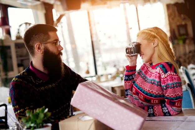 テーブルの上のプレゼントと彼女のボーイフレンドの写真を撮る美しいブロンドの女の子。