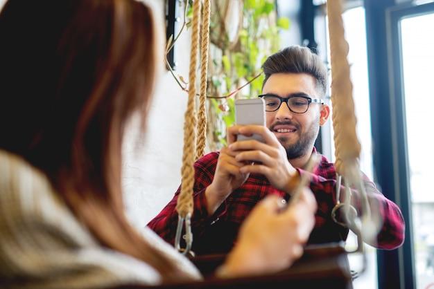 Автопортрет, делая в ресторане пара, наслаждаясь вместе. фотография мобильного позирования для социальных сетей.