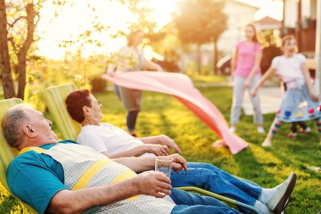 祖父母が横になっていると裏庭で休んでいます。バックグラウンドで孫が遊んでいます。家族の集まりのコンセプトです。
