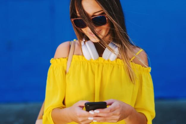 Милая девушка в желтой рубашке стоя перед синей стеной и держа сотовый телефон с улыбкой на лице.