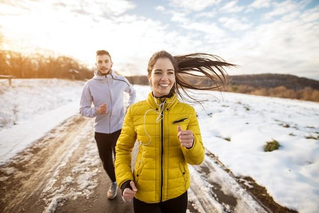 Активные спортсмены спортивной пары бегут с сильной настойчивостью по дороге в зимнюю природу по утрам.
