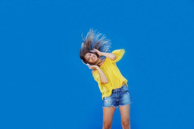 Милая кавказская девушка в желтой блузке и джинсовых шортах наслаждается музыкой