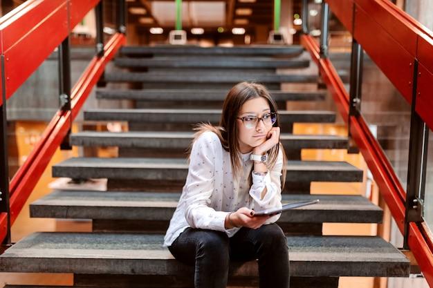 茶色の髪と手に寄りかかって階段に座っている眼鏡の退屈なコラージュの女の子