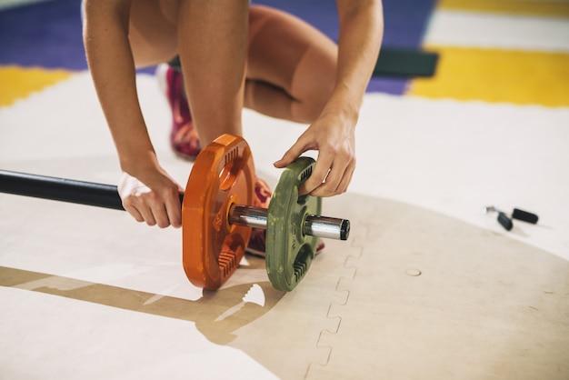 運動のための重みを入れてジムの女の子。